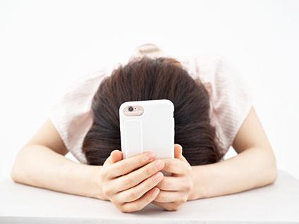 スマートフォンを手に顔を伏せる女性