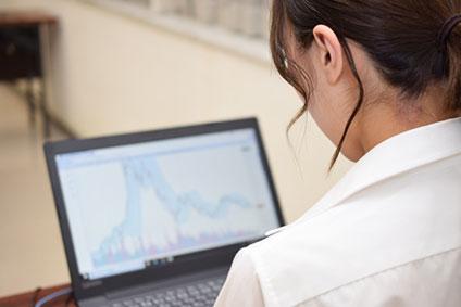 PCのチャートを見つめる女性