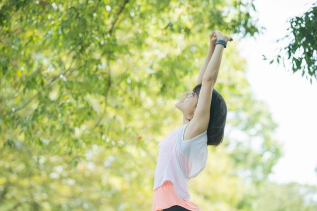 自然の中、背伸びをする女性