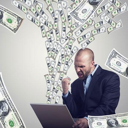 パソコンを使ってお金を稼ぎガッツポーズしている男性