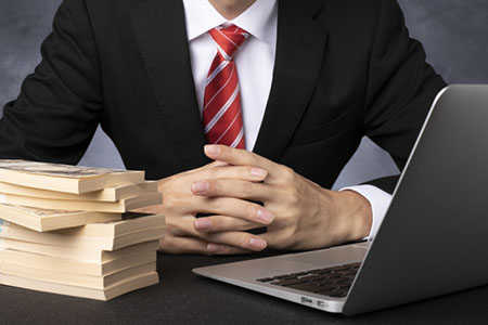 大金とパソコンを前にするスーツ姿の男性