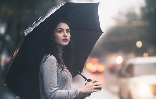 雨の中、傘をさしている女性