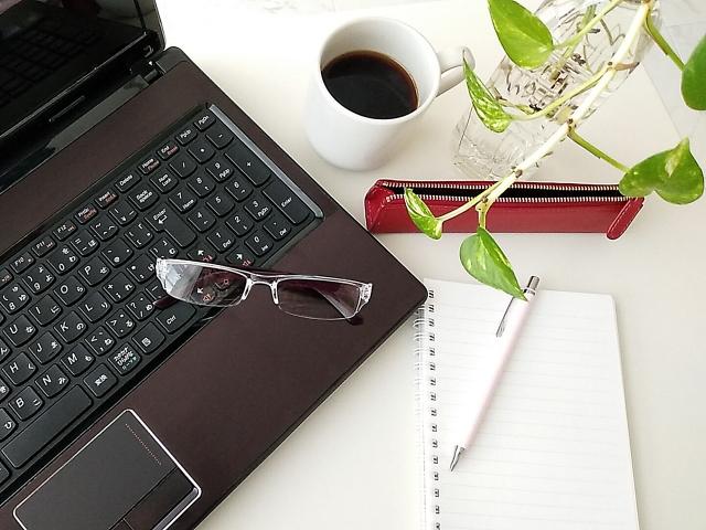 パソコンと眼鏡とノートとペン