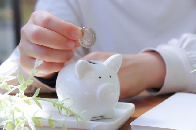 豚の貯金箱にお金を入れる